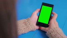 Woman looking at smartphone with green screen stock video footage