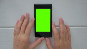 Woman looking at smartphone with green screen. Woman looking at vertical smartphone with green screen. Close up shot of woman`s hands with mobile. White wooden stock video
