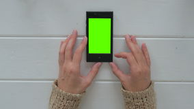 Woman looking at smartphone with green screen. Woman looking at vertical smartphone with green screen. Close up shot of woman`s hands with mobile. White wooden stock footage