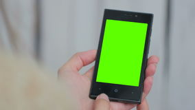 Woman looking at smartphone with green screen. Woman looking at vertical smartphone with green screen. Close up shot of woman`s hands with mobile. White wooden stock video footage