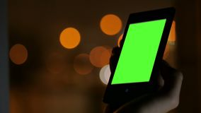 Woman looking at smartphone with green screen. Woman looking at vertical smartphone with green screen at night. Blurred traffic bokeh light. Chroma and stock video