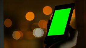 Woman looking at smartphone with green screen. Woman looking at vertical smartphone with green screen at night. Blurred traffic bokeh light. Mock up and Stock Photo