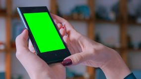 Woman looking at smartphone with greenscreen