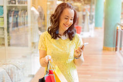 Woman looking at smartphone while shopping Royalty Free Stock Image