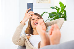 Woman looking a smartphone and smiling at home Stock Images