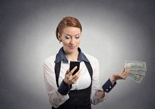 Woman looking at smartphone throwing away cash dollar bills. Happy business woman looking at smart phone throwing away cash dollar bills isolated grey wall Royalty Free Stock Images