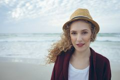 Woman looking and smiling at camera standing on the beach. Portrait of beautiful young Caucasian woman  with hat standing on the beach. She is smiling and stock image