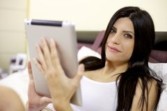 Woman looking and smiling while reading tablet Royalty Free Stock Image