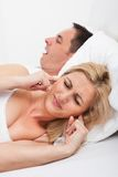 Woman looking at snoring man. Portrait Of An Angry Woman Awaken By Her Boyfriend's Snoring Royalty Free Stock Photo