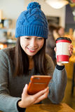 Woman looking something funny on cellphone. At coffee shop stock photo