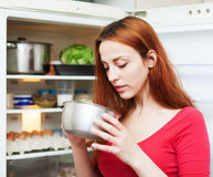 Woman looking for something in pan near fridge Royalty Free Stock Photography
