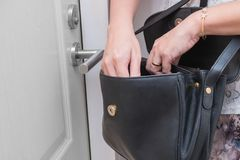Woman looking for something such as keys in her handbag in front of her apartment stock image
