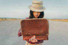 Woman looking for something in suitcase. Young beautiful woman looking for something in the open suitcase, theme of travel Royalty Free Stock Photo