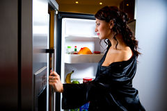 Woman looking for something to eat. Young woman looking for something to eat inside the fridge Royalty Free Stock Photo