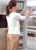 Woman looking for something to eat. Young woman looking for something to eat Royalty Free Stock Images