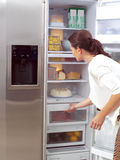 Woman looking for something to eat. Young woman looking for something to eat stock image