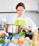 Woman looking at spoiled food in kitchen. Woman in kitchen looking into a pan and seeing spoiled food in there Royalty Free Stock Image