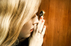 Woman looking into spy hole.  Royalty Free Stock Image