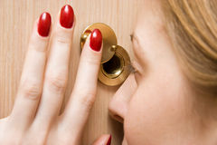Woman looking into spy hole closeup Stock Photography