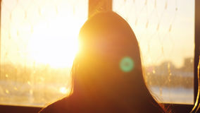 Woman looking standing near the window with view on sunset in city and lense flare effects Stock Photography