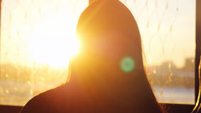 Woman looking standing near the window with view on sunset in city and lense flare effects Royalty Free Stock Photos