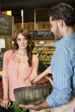Woman looking at store clerk in supermarket Stock Photo