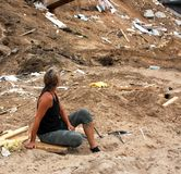 Woman looking at storm damage. Woman sitting on the ground looking at severe storm damage royalty free stock image