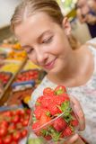 Woman looking at strawberries in shop Royalty Free Stock Photography