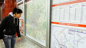 Woman looking at subway metro map. Hamburg, Germany - October, 10, 2016: Young woman looking at subway metro underground tube map on train station. Tourist use Stock Images