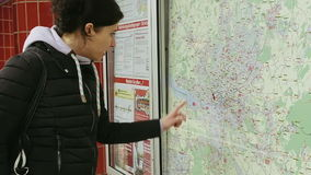 Woman looking at subway metro map. Hamburg, Germany - October, 10, 2016: Young woman looking at subway metro underground tube map on train station. Tourist use stock video