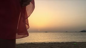 Woman looking at the sunset at the sea stock footage