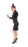 Woman looking surprised at her cellphone. A shocked young woman in a black dress and long necklace looking with an open mouth at her phone, isolated for white royalty free stock photography