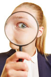 Woman looking suspicious through magnifying glass Royalty Free Stock Photo