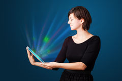 Woman looking at tablet with abstract lights Royalty Free Stock Photo