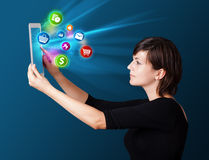 Woman looking at tablet with colorful icons Stock Photos