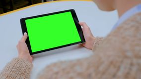 Woman looking at tablet computer with green screen at home. Over shoulder view - woman looking at black digital tablet computer device with empty green screen on stock footage
