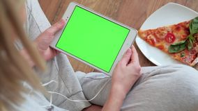 Woman looking at tablet computer with green screen in home stock footage