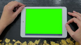 Woman looking at tablet computer with green screen stock video