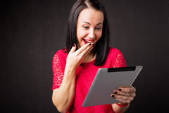 Woman looking at tablet and covering her mouth in surprise Stock Image