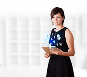 Woman looking tablet with currency icons. Young business woman looking at modern tablet with currency icons Royalty Free Stock Photography