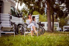 Family vacation travel, holiday trip in motorhome RV. Woman looking at the tablet near the camping . Caravan car Vacation. Family vacation travel, holiday trip stock photo