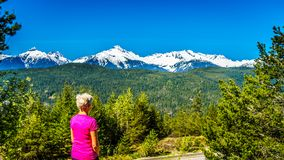 Woman looking at the Tantalus Mountain Range with snow covered peaks of Alpha Mountain, Serratus and Tantalus Mountain. Seen from a viewpoint along the Sea to Royalty Free Stock Photography
