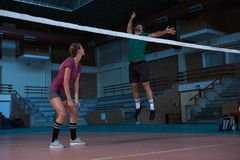 Woman looking at teammate jumping at volleyball court Stock Image