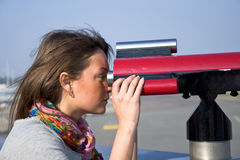 Woman looking through a telescope Stock Images