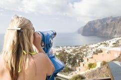 Woman looking through telescope at sea Stock Photo
