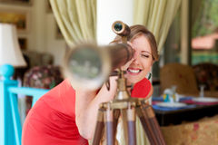 Woman looking through the telescope and smiling Stock Photo