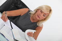 Woman looking through text books Stock Photography