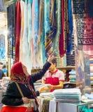 Woman looking textiles, Grand Bazaar stock photo