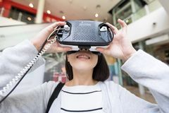 Woman looking though virtual reality device. Beautiful young asian woman Royalty Free Stock Photo