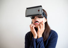 Woman looking though virtual reality device and feeling scar Royalty Free Stock Photography